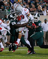 Ohio State Buckeyes running back Jalin Marshall (17) leaps between Michigan State Spartans safety RJ Williamson (26) and safety Kurtis Drummond (27) during the second quarter of the NCAA football game at Spartan Stadium in East Lansing, Michigan on Nov. 8, 2014. (Adam Cairns / The Columbus Dispatch)