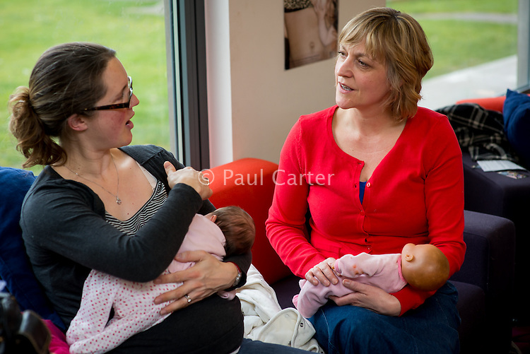 A midwife, using a doll to demonstrate, discusses breastfeeding techniques with a young woman at a drop-in breastfeeding support centre.<br /> <br /> Image from the breastfeeding collection of the &quot;We Do It In Public&quot; documentary photography picture library project: <br />  www.breastfeedinginpublic.co.uk<br /> <br /> Hampshire, England, UK<br /> 13/03/2013<br /> <br /> &copy; Paul Carter / wdiip.co.uk