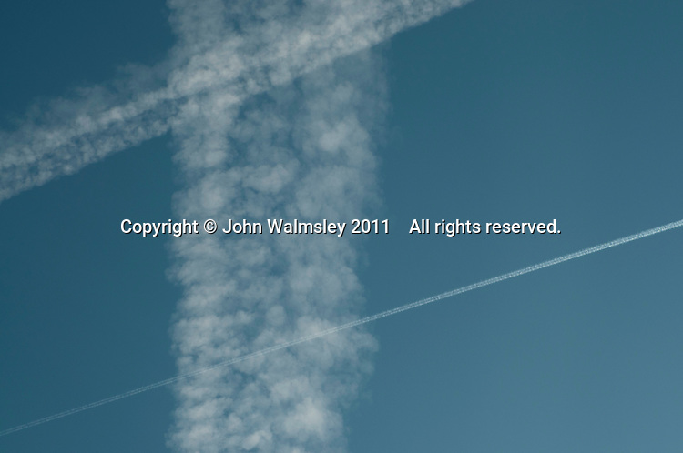Contrails or water condensation trails from an aircraft's jet engines, high above the Southeast of England.  They begin very narrow and widen as the winds spread them out.
