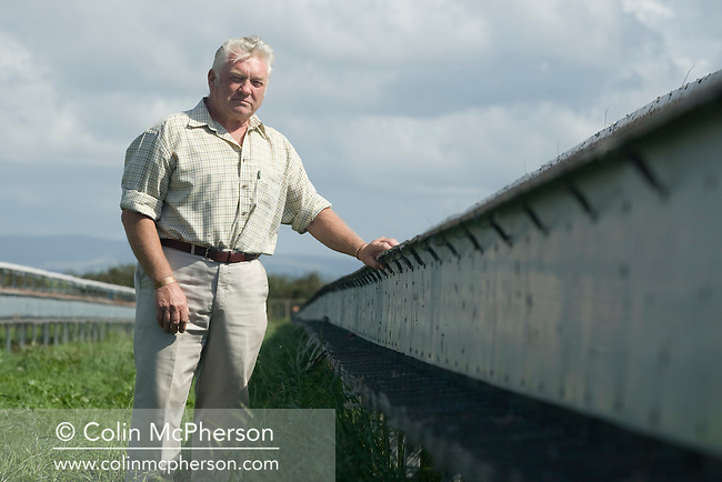 Ray Holden, owner of Hy-Fly Hatcheries, a company based in Preesall, near Blackpool, Lancashire which specialises in breeding partridge and pheasant to be sold to sporting estates, pictured standing next to raised cage laying units containing partridges. The partridges are kept in small cages for up to three years while they mature before being sold. Pheasants are also kept in cages but are transferred to outdoor pens as they mature. The company produces around three million day-old chicks per year.