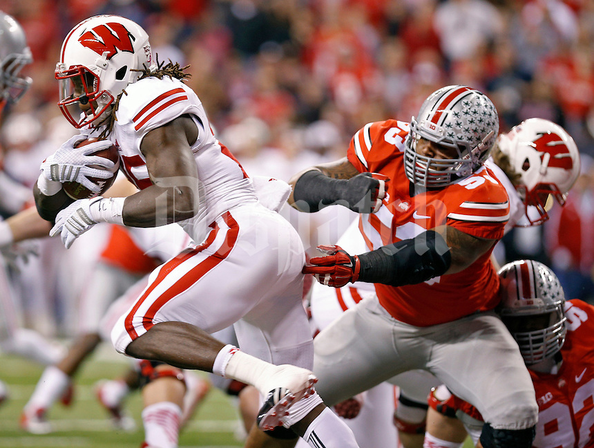 Wisconsin Badgers running back Melvin Gordon (25) gets away from Ohio State Buckeyes defensive tackle Michael Bennett (53) on a rush during the 1st quarter in the 2014 Big Ten Football Championship Game at Lucas Oil Stadium in Indianapolis, Ind. on December 6, 2014.  (Dispatch photo by Kyle Robertson)