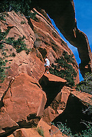 Teenage girl posing proudly in arch. Utah United States Wall Arch.