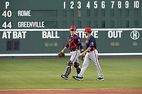 Starting pitcher Odalvi Javier (40) of the Rome Braves, right, walks from the dugout with catcher Logan Brown (99) before a game against the Greenville Drive on Friday, April 19, 2019, at Fluor Field at the West End in Greenville, South Carolina. Greenville won, 2-0. (Tom Priddy/Four Seam Images)