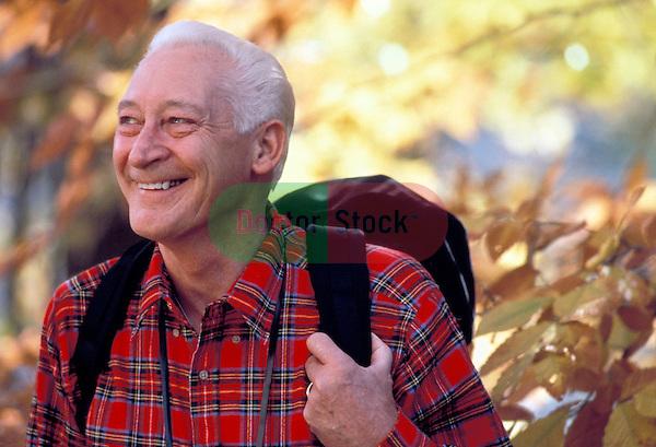 smiling healthy elderly man hiking in autumn woods