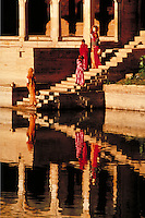 Scenic view of stairway leading to river with graceful women in colorful saris balance water urns on their heads and arms.