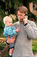 Father talking on cell phone holding son ages 35 and 2.  St Paul Minnesota USA