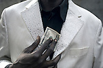 "KINSHASA, DEMOCRATIC REPUBLIC OF CONGO - FEBRUARY 12: Jika, a senior Sapeur shows a USA one hundred dollar bill while wearing his white diamond suit close to his home in the Mombele area on February 12, 2012 in Kinshasa, DRC. Jika loves Japanese fashion especially the designer Yohji Yamamoto. The word Sapeur comes from SAPE, a French acronym for Société des Ambianceurs et Persons Élégants or Society of Revellers and Elegant People and it also means, to dress with elegance and style"". Most of the young Sapeurs are unemployed, poor and live in harsh conditions in Kinshasa,  a city of about 10 million people. For many of them being a Sapeur means they can escape their daily struggles and dress like fashionable Europeans. Many hustle to build up their expensive collections. Most Sapeurs could never afford to visit Paris, and usually relatives send or bring clothes back to Kinshasa. (Photo by Per-Anders Pettersson"