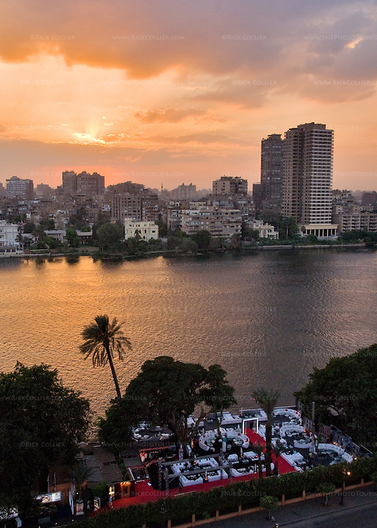 Sunset view across the waterfront street (the Corniche du Nile), an open-air restaurant, and the Nile River from a balcony at the Conrad Hilton, Cairo, Egypt.