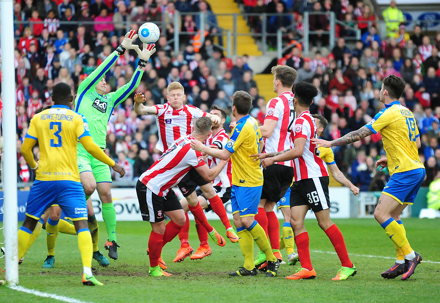 Torquay United's Brendan Moore collects the ball under pressure from Lincoln City's Elliott Whitehouse<br /> <br /> Photographer Andrew Vaughan/CameraSport<br /> <br /> Vanarama National League - Lincoln City v Torquay United - Friday 14th April 2016  - Sincil Bank - Lincoln<br /> <br /> World Copyright &copy; 2017 CameraSport. All rights reserved. 43 Linden Ave. Countesthorpe. Leicester. England. LE8 5PG - Tel: +44 (0) 116 277 4147 - admin@camerasport.com - www.camerasport.com