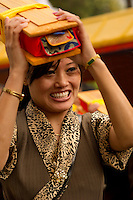 Devotee carryong scrolls in a Losar procession at a Buddhist  Monastery, Sikkim, India