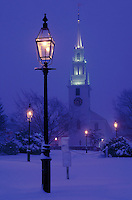 USA, Newport, RI -Trinity Church in a winter snow fall with gas lamps in Queen Anne's Square.