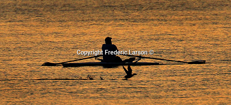 A rower on a small craft gets his early-morning exercise on San Francisco's Bay, California.