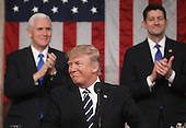 Vice President Mike Pence (L) and Speaker of the House Paul Ryan (R) applaud as US President Donald J. Trump (C) delivers his first address to a joint session of Congress from the floor of the House of Representatives in Washington, DC, USA, 28 February 2017.  Traditionally the first address to a joint session of Congress by a newly-elected president is not referred to as a State of the Union.<br /> Credit: Jim LoScalzo / Pool via CNP