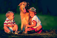 Two young boys sitting outside with their dog.