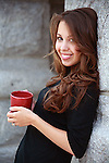 pretty young woman with long brown hair smiles and holds a coffee cup outdoors in morning shade
