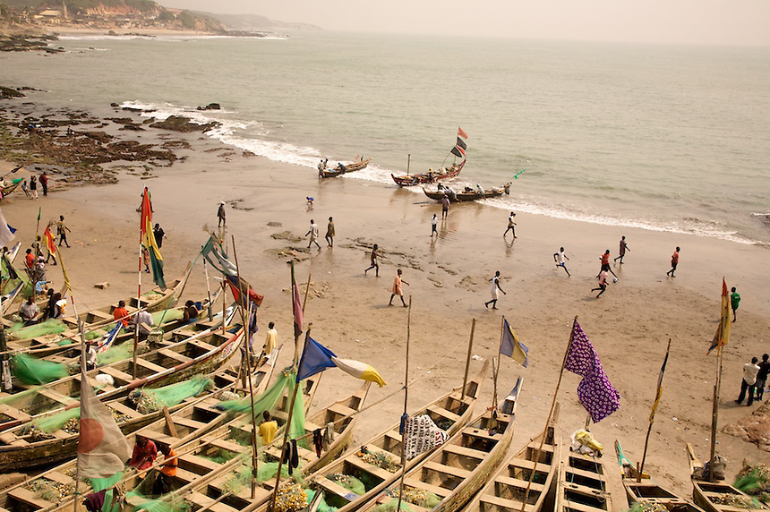 Fishermen beside Cape Coast Castle, Ghana. Small boys play soccer on the beach. Photograph by Peter Randall.