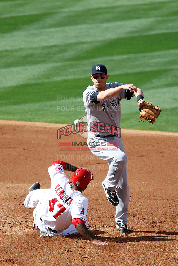 Reid Brignac #40 of the New York Yankees turns a double play while avoiding the slide by Howie Kendrick #47 of the Los Angeles Angels during a game at Angel Stadium on June 15, 2013 in Anaheim, California. (Larry Goren/Four Seam Images)