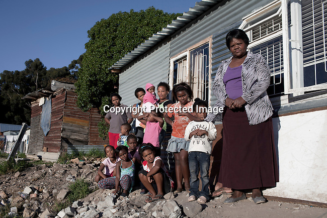 CAPE TOWN, SOUTH AFRICA - APRIL 19: Veronica Daniels stands outside her home with her daughters and grandchildren in Imizamo Yethu,  a poor township on April 19, 2011 in Hout Bay outside Cape Town, South Africa. (Photo by Per-Anders Pettersson)