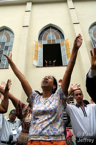 A woman raises her arms while praying at a Methodist church in Havana. Public expression of religious faith has steadily increased since the Cuban government ended its status as an officially atheist state in the early 1990s.