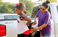 NWA Democrat-Gazette/DAVID GOTTSCHALK  Chakya Woods, a fourth grade student a Owl Creek School, receives last minute help with her backpack from her mother Natasha Barber before  the first day at the  continuous learning school Tuesday, August 4, 2015 in Fayetteville. Schools on the traditional learning calendar will begin Monday, August 17.
