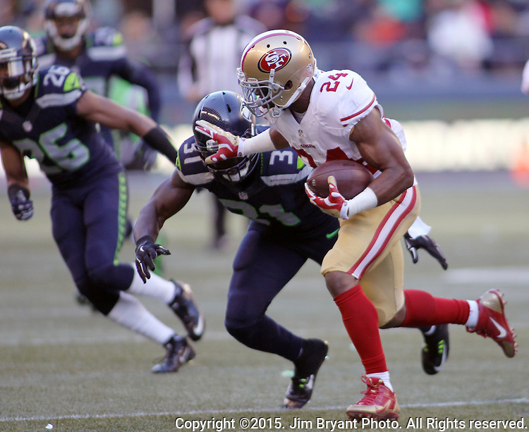 San Francisco 49ers running back Shaun Daughn (24) stiff arms Seattle Seahawks strong safety Kam Chancellor (31) at CenturyLink Field in Seattle, Washington on November 22, 2015.  The Seahawks beat the 49ers 29-13.   ©2015. Jim Bryant Photo. All RIghts Reserved.