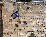 The Israeli flag with the Star of David flies next to the Western Wall of the Temple Mount in the Jewish Quarter of the Old City of Jerusalem.  The Old City of Jerusalem and its Walls is a UNESCO World Heritage Site
