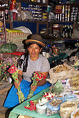 Peru. Woman wearing typical bowler hat selling seeds, flowers, drinks, eggs (food) on the market.