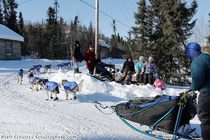Village school kids take an outing to watch Iditarod musher Bruce Linton race down the street at the Shageluk village checkpoint during the 2011 Iditarod race..