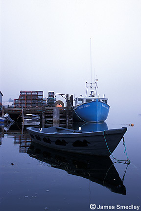 Fishing boats docked with lobster traps on dock