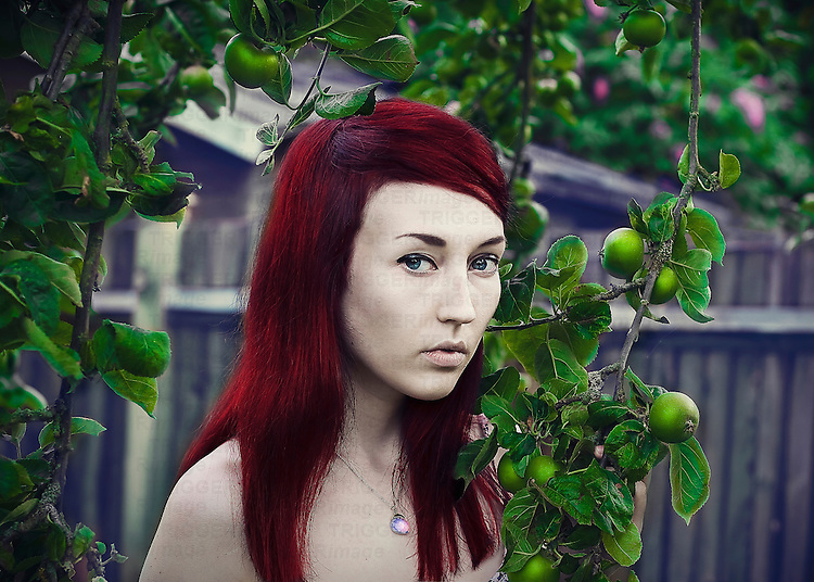 Young woman with red head and blue eyes and pale skin, holding a green apple tree branch, with garden background.