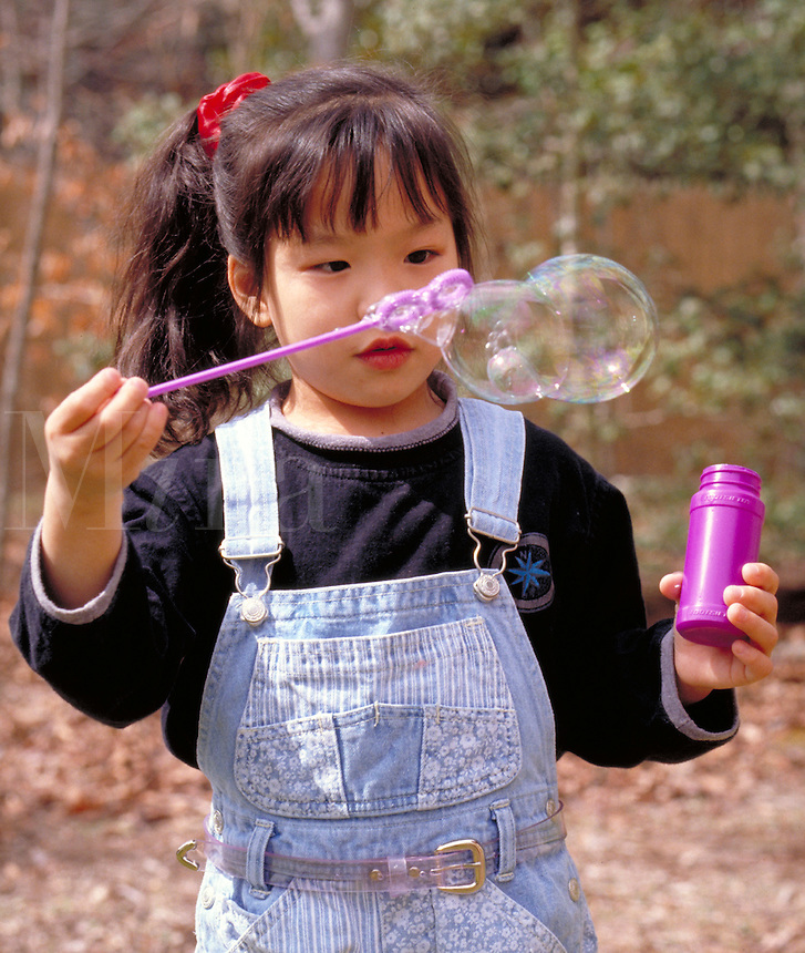 5 year old Asian-American girl playing with soap bubbles. Kids, children, fun. Kimberly.