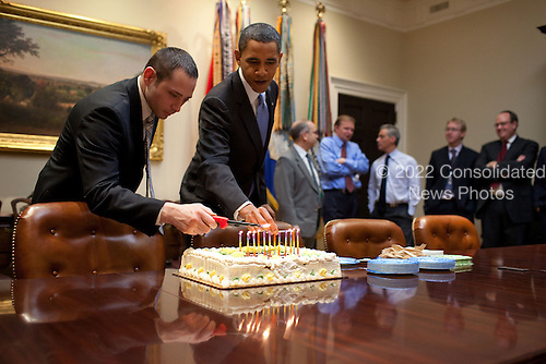 Washington, DC - December 2, 2009 -- United States President Barack Obama and Oval Office Valet Raymond Rogers light candles on a birthday cake for National Security Council (NSC) Chief of Staff Denis McDonough in the Roosevelt Room of the White House, Tuesday, December 2, 2009.  .Mandatory Credit: Pete Souza - White House via CNP