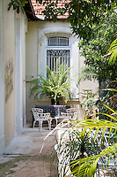 A pair of wrought-iron chairs has been placed in a sunny spot in the garden