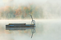 Fog on Horseshoe Lake in autumn with dock, Near Parry Sound, Ontario, Canada