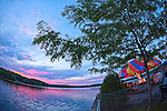AUG. 25, 2012 - MIDDLEBURY, CONNECTICUT, U.S. - Sunset over Lake Quassipaug, also known as Lake Quassy, in Connecticut, USA, with Quassy Amusement Park lighted ride at right. Summer sunset panorama taken with 180 degree fisheye lens.