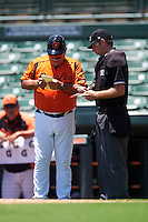 GCL Orioles manager Orlando Gomez (23) goes over the lineup with umpire Ross Sheridan during a game against the GCL Twins on August 11, 2016 at the Ed Smith Stadium in Sarasota, Florida.  GCL Twins defeated GCL Orioles 4-3.  (Mike Janes/Four Seam Images)