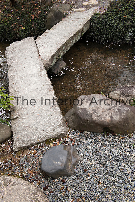 A small footbridge fashioned out of slabs of stone crosses a stream