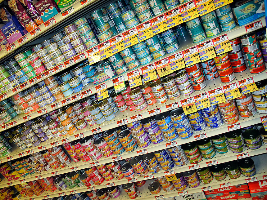 Variety of canned cat food products on a store shelf.