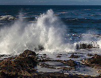 A wave crashing into the rocky shore creates a reverse waterfall, shooting spray high over the rugged Bean Hollow State Beach.