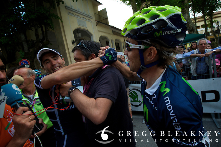 Francisco Ventoso celebrates with a Movistar teammate after his stage 6 victory.  This TV reporter managed to get his wires tangled in the middle of Movistar's moment.