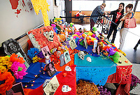 NWA Democrat-Gazette/DAVID GOTTSCHALK  Cecilia Grossberger (center), with New Student and Family Programs at the University of Arkansas, describes the Altar of Death put on display Monday, November 2, 2015, recognizing Dia de Los Muertos, Day of the Dead, in the Student Union on the campus in Fayetteville. The display and other activities were sponsored by the University Hispanic Heritage Month committee recognized the Central and South American holiday.