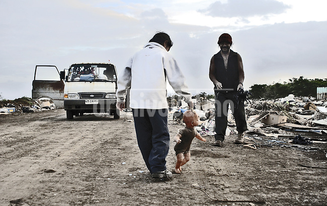 Cacho inspecting the rubbish dump of the Island. each day when the Lanchile flight leave he goes and serch for food for his chikens, and whatever he can find for his house he is building  Hanga Roa, the only village of the Island. After 5 days as a tourist, photographer Lorenzo Moscia set to discover the real life of one of the more surprising places of the World, mix of cultures between Oceania and Latin America, with a native population near extintion./ Pepka Icka Contreras, Cacho`s doughe plaing with a dolly she found in the rubbish dump. Lorenzo Moscia/
