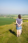 Woman standing on steep chalk scarp slope Cherhill Down, Wiltshire, England, UK looking towards the village of Cherhill in the clay vale