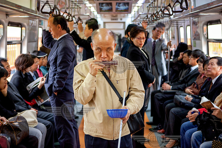 A blind man begs for money by playing a harmonica on a metro train in Seoul.