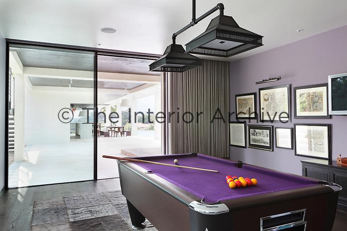 A mauve pool room with a matching purple felt pool table