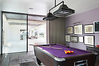 A mauve pool room with a matching purple felt pool table