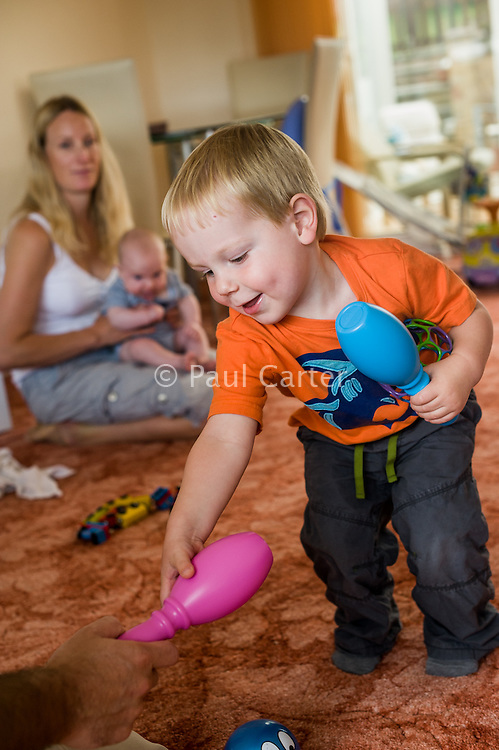 A young boy smiles as he plays with coloured plastic skittles. His mother and baby brother watch in the background...09/07/2011.Hampshire, England, UK