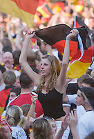 Germany, DEU, Dortmund, 2006-Jun-24: FIFA football world cup (USA: soccer world cup) 2006 in Germany; German football fans in good mood at a public viewing zone during the world cup match Germany vs. Sweden (2:0). A young woman sitting on a man's shoulders is waving a German flag.