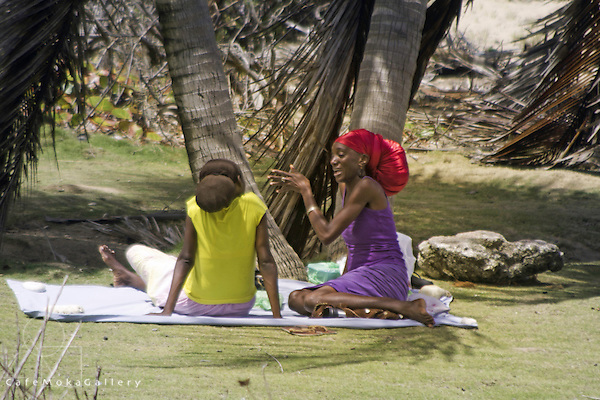Barbados - Two young women with rasta wrapped in cloth hair sit chatting under a coconut tree, Bathsheba