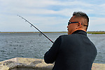 South Merrick, New York, USA. 24th May 2015. Rev. DAVID YI, of Douglaston, Queens, is fishing in Merrick Bay from the pier of Levy Park & Preserve during Memorial Day Weekend. The pastor's group went to the park because they could not go to Jones Beach to fish, for area parkways were closed after the beach filled to capacity for the Bethpage New York Air Show, which could be seen earlier from a distance in the sky behind him.